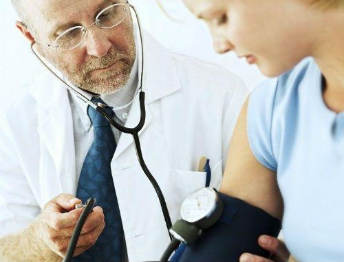лікар вимірює тиск дівчині