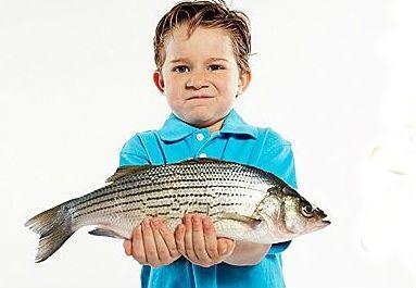 хлопчик тримає рибу в руках на білому тлі